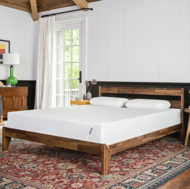 mattress on wood bedframe in bedroom