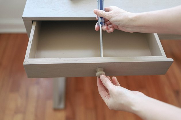 Removing drawer knob on desk with a screwdriver