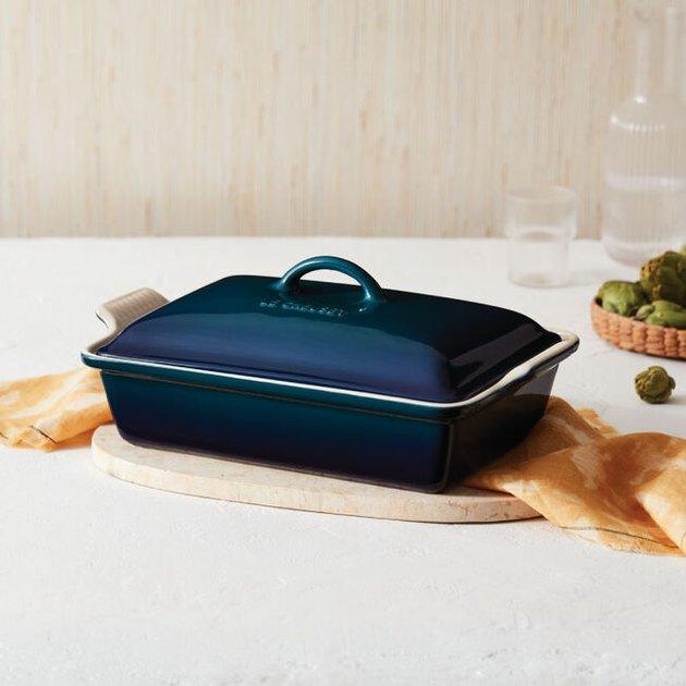 blue le creuset dish on cutting board