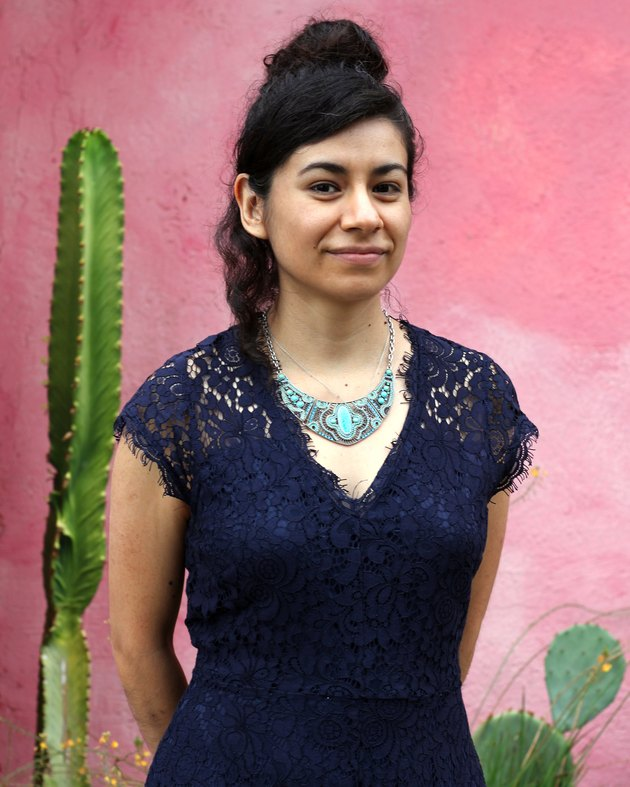 person standing near pink wall and cactus