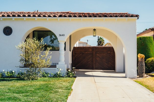 A white Spanish-style home with a red-tiled roof; curved archways cover a wooden gate and a lush green yard is in front