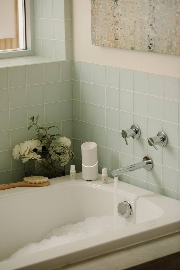 bathroom with light blue tile and white diffuser
