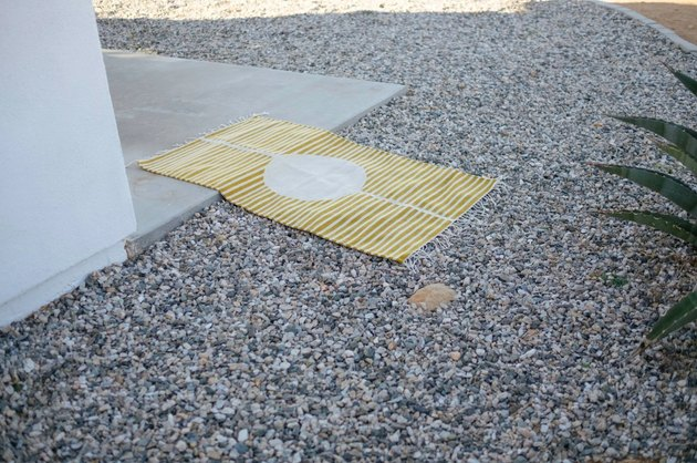Yellow and white striped eco-friendly rug laying on ground in desert