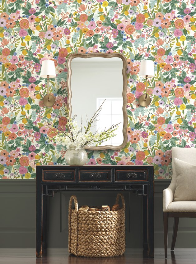 vanity area with mirror and floral wallpaper