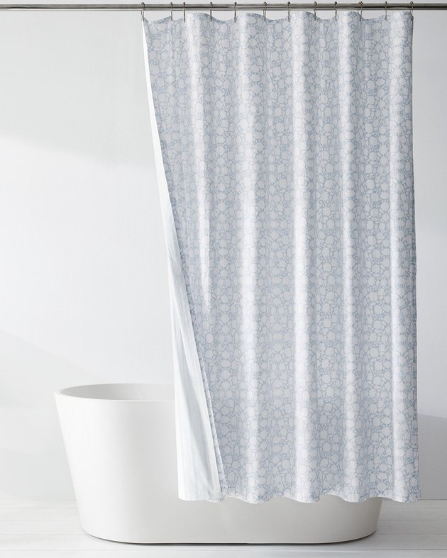 Blue and white floral reversible eco-friendly shower curtain in white bathroom