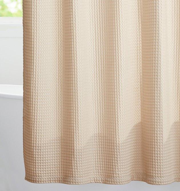 Beige waffle eco-friendly shower curtain in white bathroom with bathtub