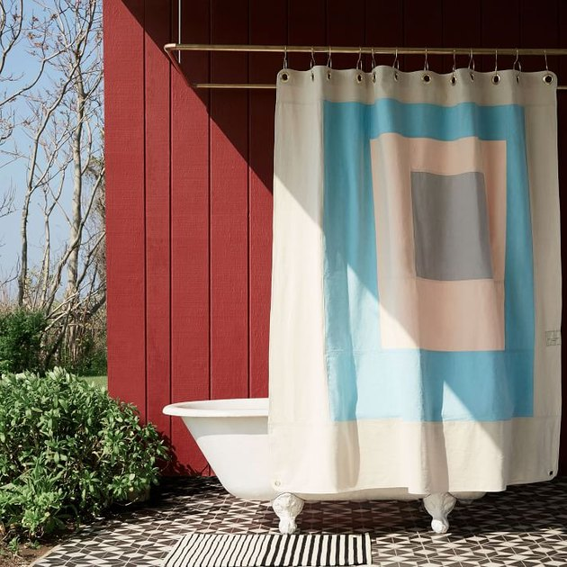 eco-friendly shower curtain with modern blue design in an outdoor bathroom against red wall
