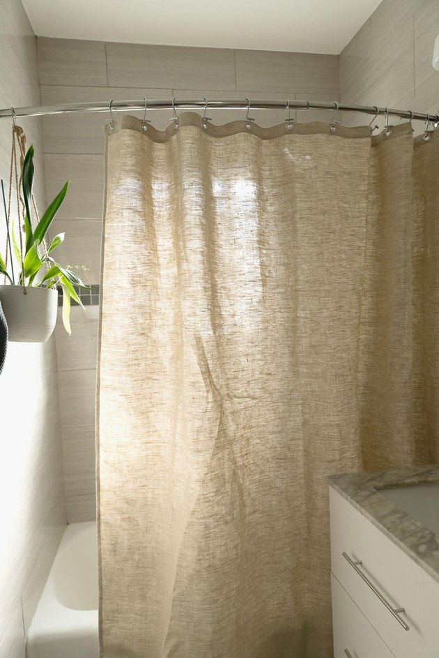 Hemp eco-friendly shower curtain pictured in sunny white bathroom with houseplant on wall