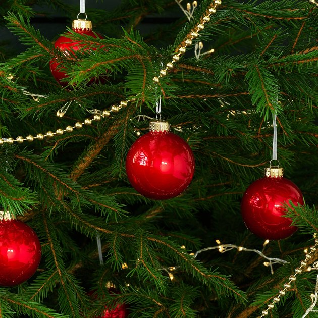 close-up of christmas tree with garland and red ornaments