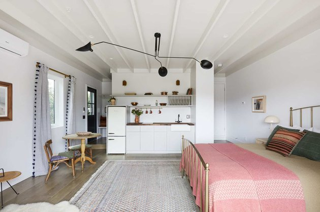 white converted garage bedroom idea with pink bedding and black pendant light