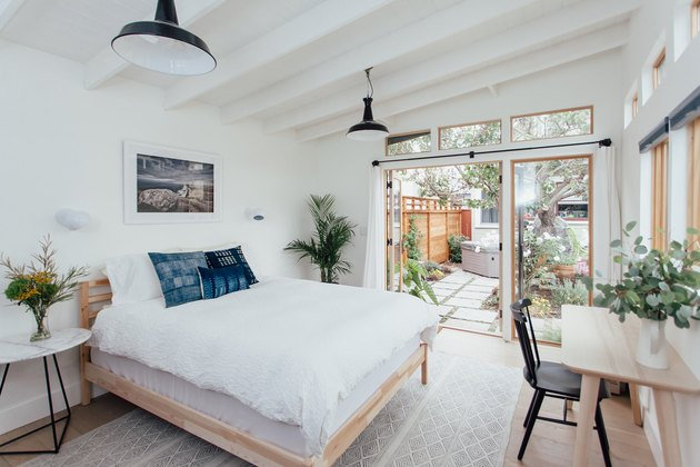 white converted garage bedroom idea with bed and wall of windows