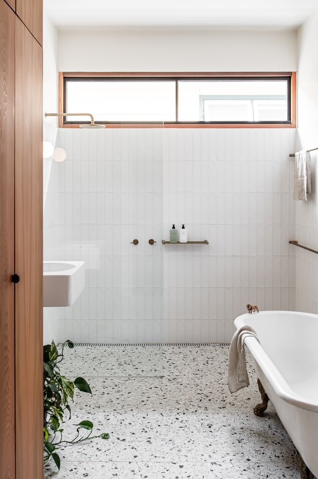 white modern bathroom with terrzzo floors and a clawfoot tub next to a standing shower