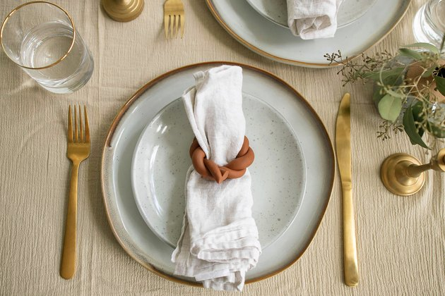 Terra cotta napkin ring on table setting with gold cutlery and ceramic plate