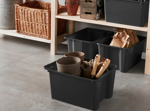 Black plastic storage containers in garage with outdoor essentials