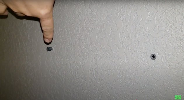 silver screws in white wall with finger pointing at one
