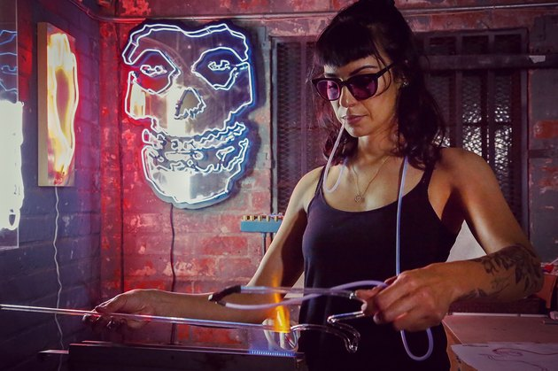 Neon artist Leticia Maldonado in her art studio with skull art in the background