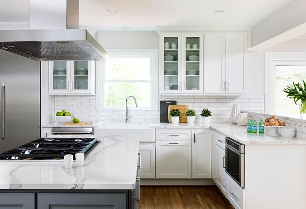 White kitchen design with an island stovetop and range hood designed by Case Designs.