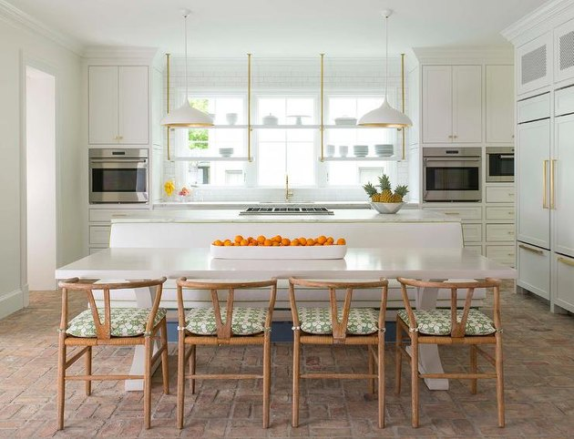 Contemporary white kitchen with an island stovetop designed by Jenkins Interiors.