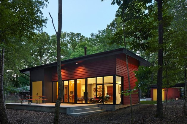red modular home in a forest with eco-friendly home design
