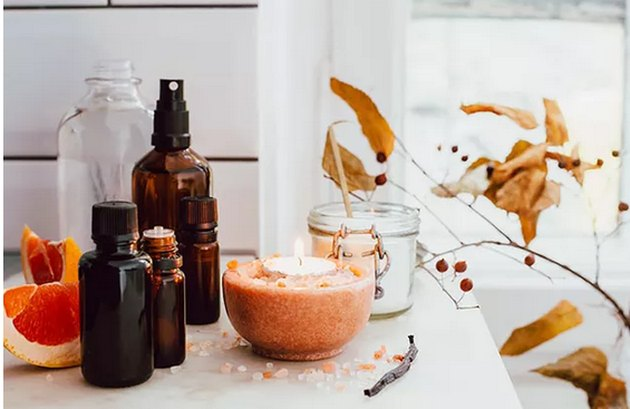 Candles and essential oils bottles on counter in autumnal colors