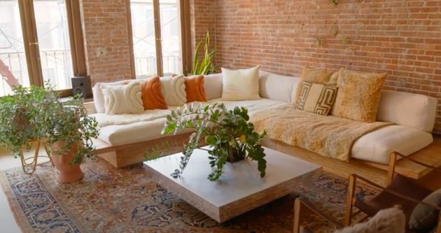 living room space with couch and plants and brick wall