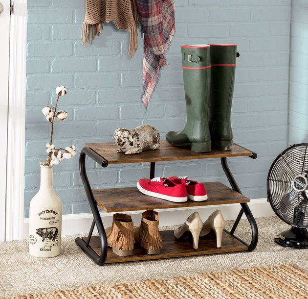 Rustic shoe organizer, rubber boots, shoes, fan, vase with dried flowers.