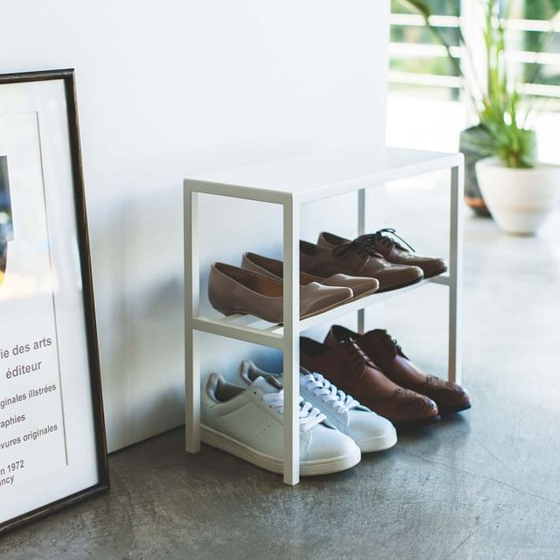White metal shoe organizer, shoes, concrete floors.
