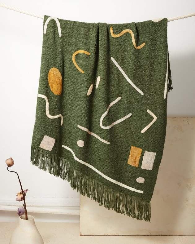 sustainable home decor with green patterned blanket hanging