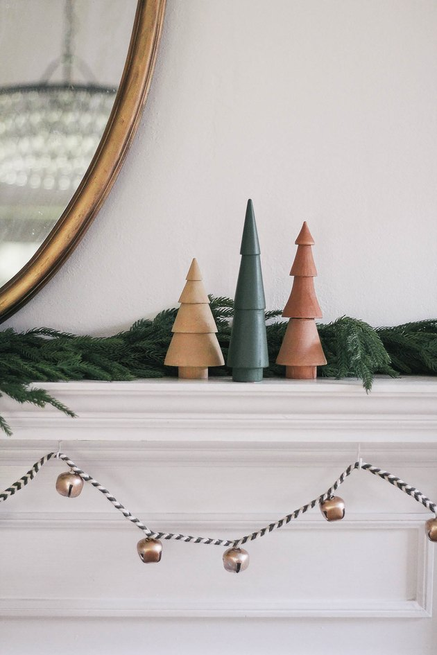 DIY sleigh bell garland hung under mantel decorated with wooden Christmas trees