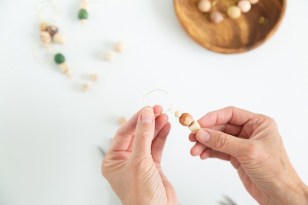 Putting wood and clay beads onto jewelry wire