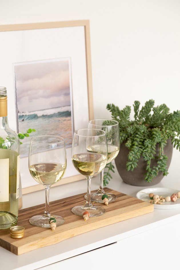 Wine glasses with clay and wood wine charms on display