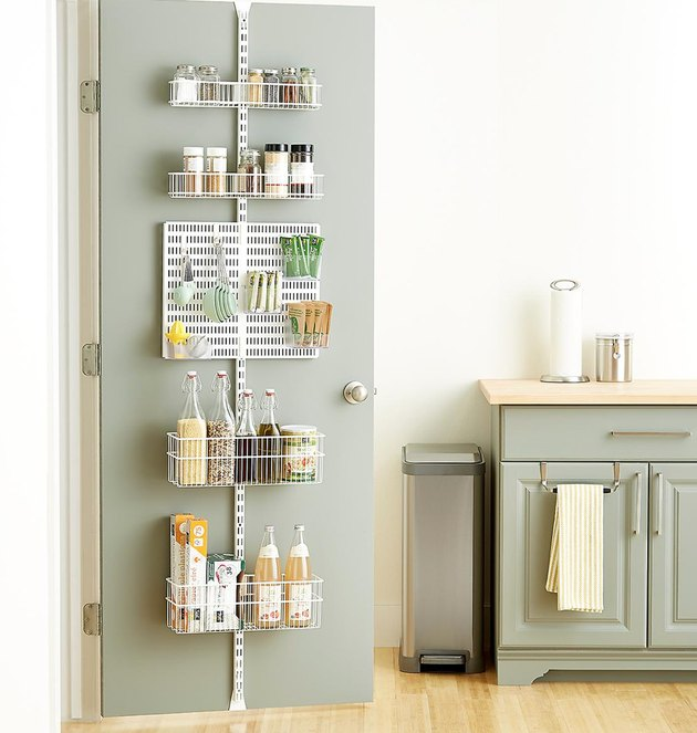 Over the Door Storage with White metal over the door organizer, sage green door and cabinets.