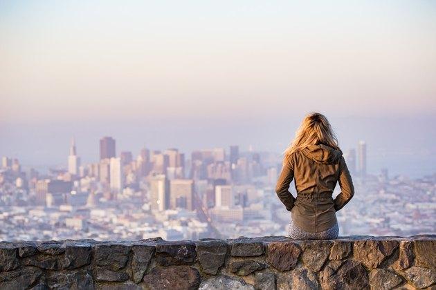 woman on rock platform looking at san francisco cityscape