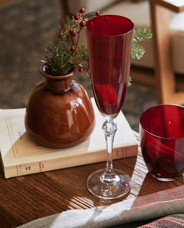 red sparkling wine flute near vase with greenery