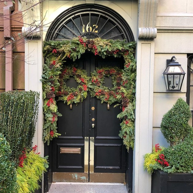 black front door with festive greenery