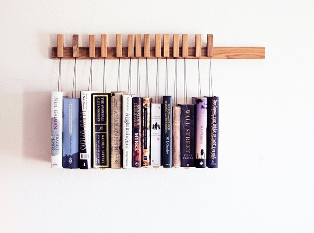 Wood book rack mounted on wall with books hanging from string
