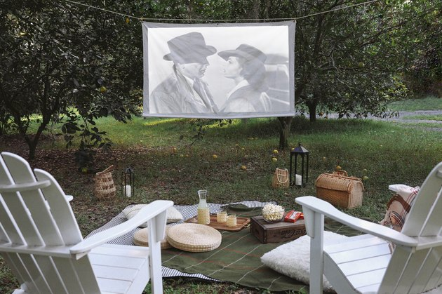 DIY portable projector screen hanging outside between two trees with chairs, blankets and snacks set in front