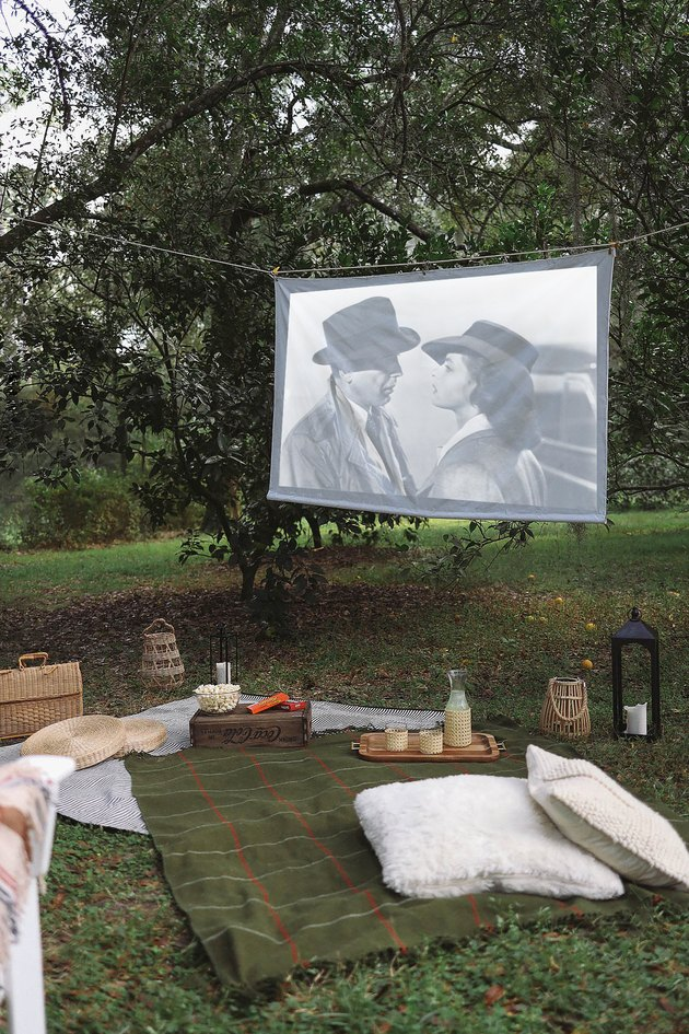 DIY portable projector screen hanging outdoors between trees with blankets and snacks set up below