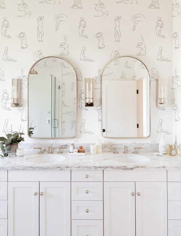 bathroom space with double mirrors and minimalist nude figures wallpaper