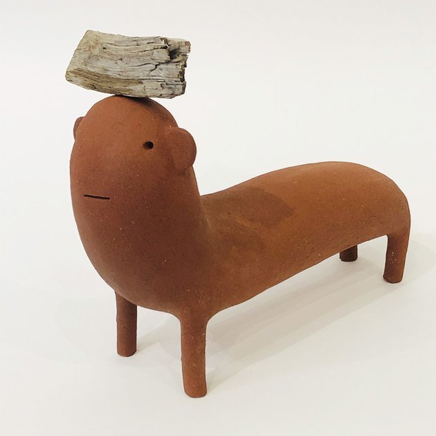 Handcrafted rust-colored ceramic sculpture of imaginary animal with piece of wood on its head by Godeleine de Rosamel.