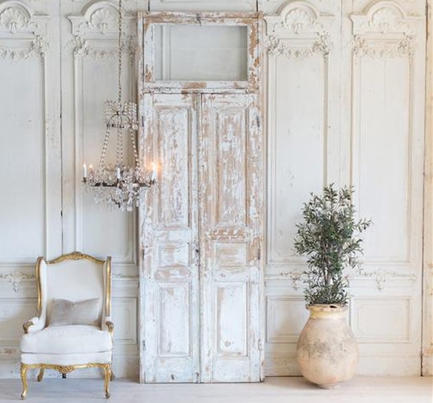 White weathered double doors with frame in white room next to white upholstered chair and potted planr