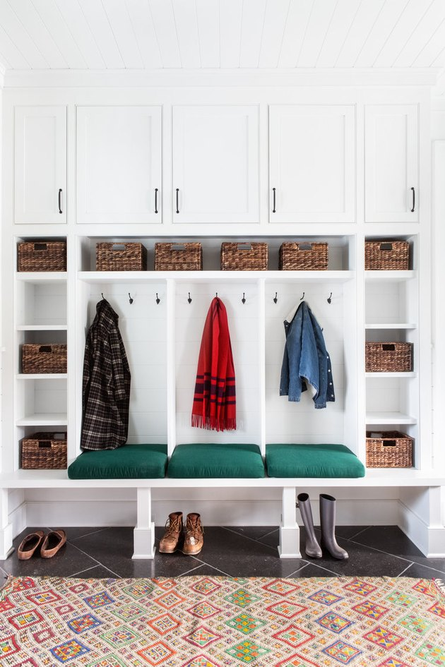mudroom storage with white cabinets, slate floor and eclectic rug