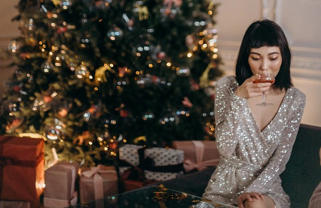 woman on sofa in sparkly dress sipping on cocktail with christmas trees and presents in background