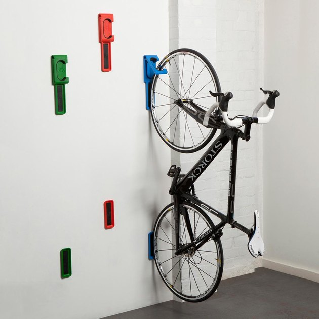 red, green, and blue bike storage hooks holding a bicycle