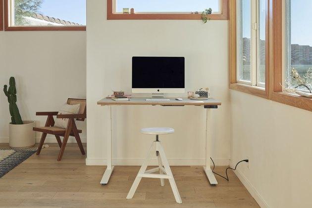 standing desk near windows and white stool