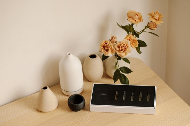 essential oils, diffuser, and roses on table