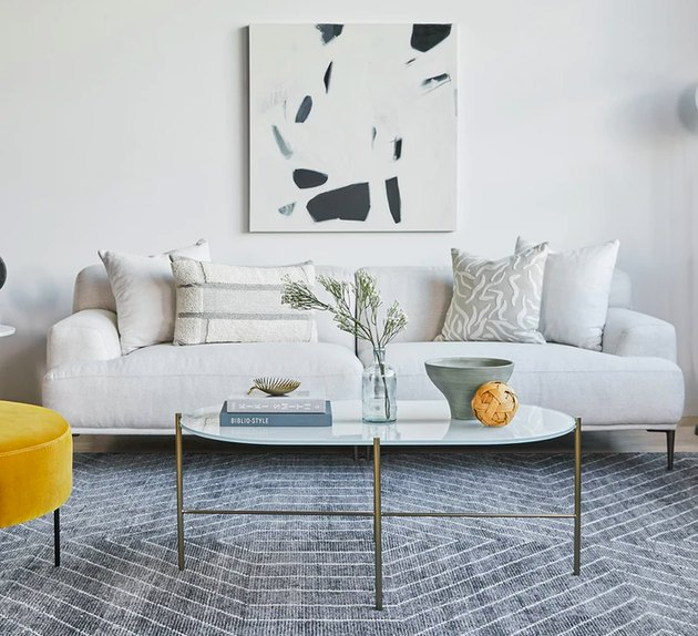 living room with white couch, gray rug, and white coffee table