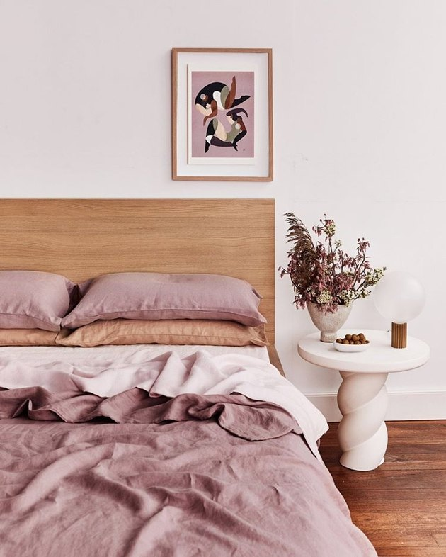 bed threads Lavender, Terracotta, and Rosewater bedding with wood headboard and white side table