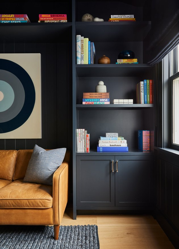 How To Organize a Bookshelf with Dark gray walls, leather couch, modern art, books, rug, wood floor.