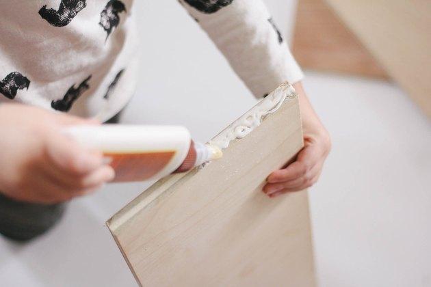 Little boy piping wood glue onto wood board